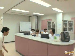 Agradável japonesa enfermeira gives um stroking para o paciente