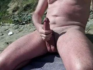 Lakuriq pederast tregon kokosh në the nudist plazh