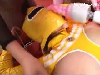 Tettona ammanettato cybergirl in yellow pvc overall getting suo tette rubbed con giocattoli fica fingered da slaves e padrona