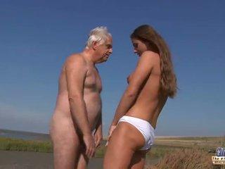 Ung bystiga goddess ridning gammal människa i en wild fan på den beach