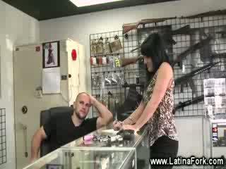 Chica seducing at a gun store