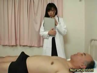 Збуджена японська медсестра gives рука робота